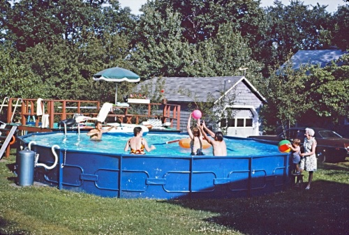 As verdant a portrait of suburbia as has ever been taken. The family is treated to a swim in the neighbors' pool, summer '75. The garage of 1107 Hope Street is in the background, as is my family's '73 Plymouth Satellite. I am the little kid stood up on the stool, clutching the beach ball.
